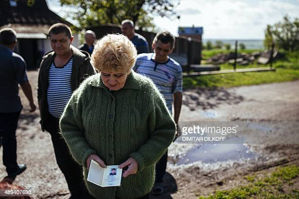 A woman holds her passport as she queues to vote for the referendum called by proRussian rebels in eastern Ukraine to split from the rest of the...