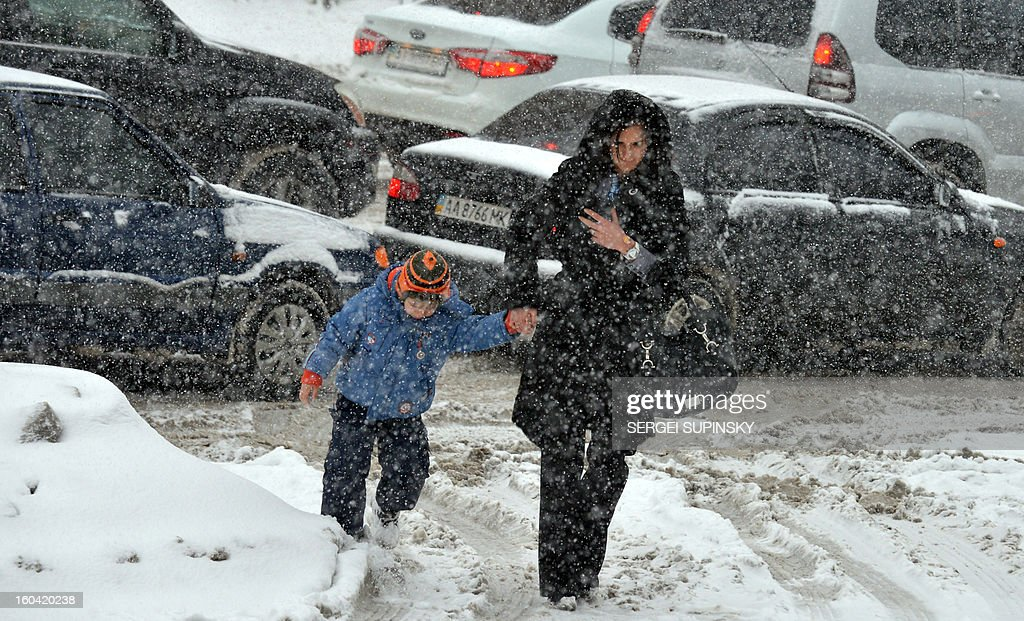 A woman holds her son as they walk during a heavy snow fall in Kiev on January 31, 2013.