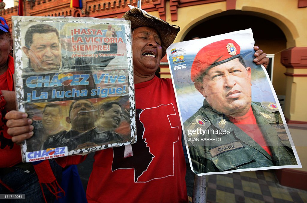 A woman holds images of the late President Hugo Chavez, during a ceremony to commemorate his birthday anniversary, in Caracas, on July 28, 2013. AFP PHOTO/Juan Barreto