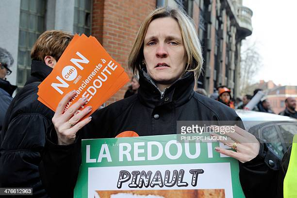 A woman holds leaflets reading 'No to layoffs at La Redoute' while several thousand employees of La Redoute mailorder company stage a protest against...