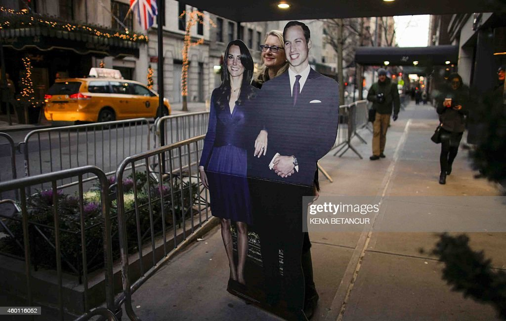A woman holds lifesize cutouts of the Duke and Duchess of Cambridge outside their Hotel on December 7 2014 in New York The threeday US trip will see...