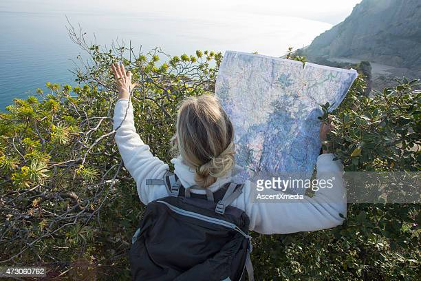 Woman holds map, peers over bushes to route ahead