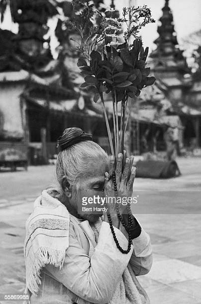 A woman holds offerings to her forehead as she prays at a temple in Burma 21st January 1950 Original publication Picture Post 4748 Inside The Temples...