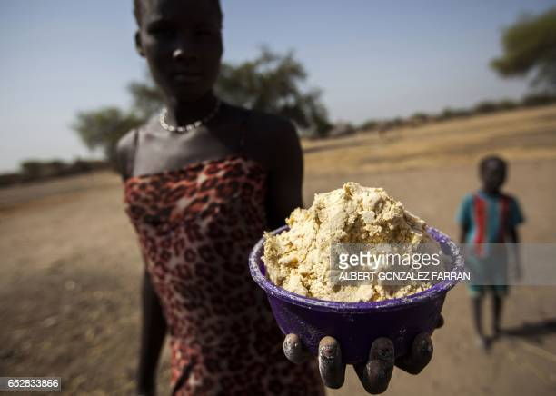 A woman holds out a bowl of partially boiled maize in Ngop in South Sudan's Unity State on March 10 2017 The Norwegian Refugee Council distributed...