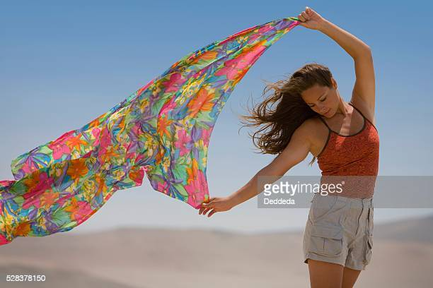 A woman holds out a scarf in the wind