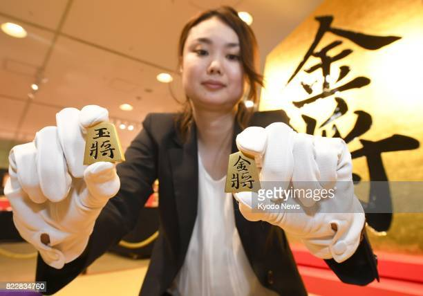 A woman holds pieces made of pure gold for shogi or Japanese chess at the Takashimaya department store in Osaka western Japan on July 26 the opening...