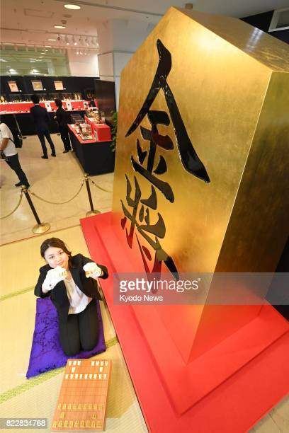 A woman holds pieces made of pure gold for shogi or Japanese chess next to a giant piece covered in leaf gold at the Takashimaya department store in...