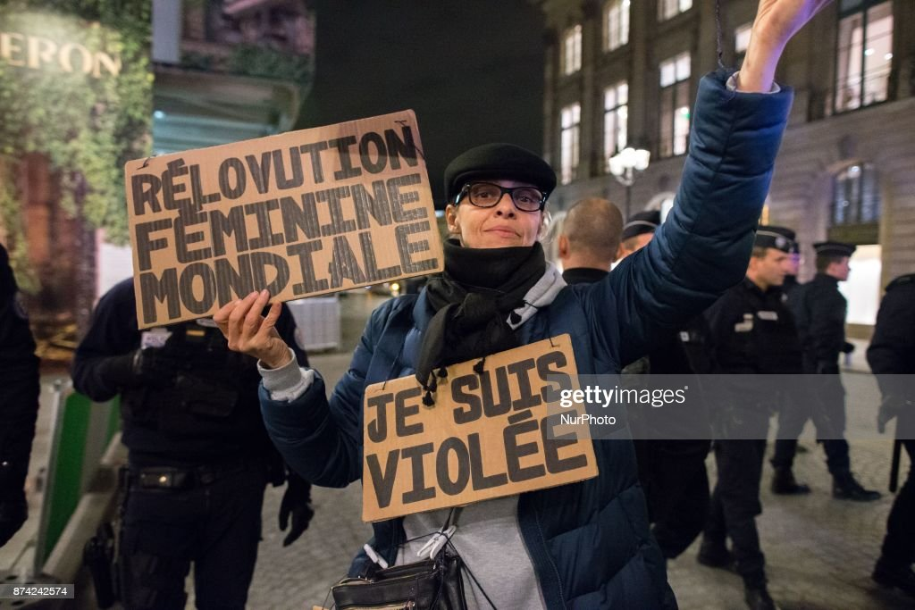 A woman holds placards reading « I am raped » (R) and « World feminine revolution » (L) as she takes part in a demonstration in front of the French Justice Ministry, in Paris, on November 14, 2017 called by different feminists associations to protest against the acquittal for rape of a man who had sex with an 11 year old. Two court decisions involving 11-year-old girls have recently highlighted the shortcomings of French law that the government intends to tackle in 2018.