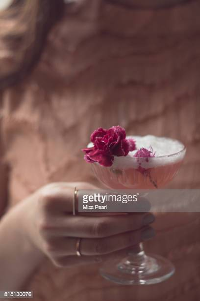Woman holds pretty drink dressed with flowers