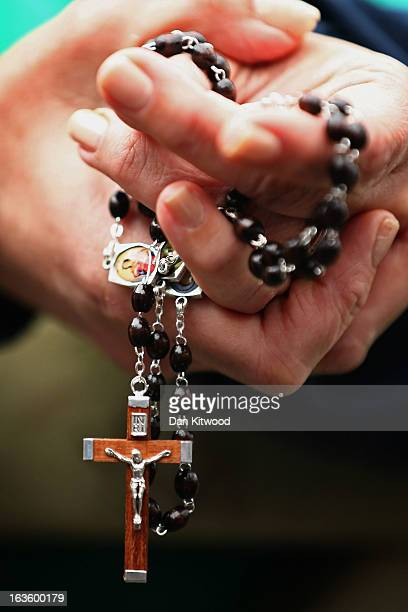 A woman holds rosary beads while she prays and waits for smoke to emanate from the chimney on the roof of the Sistine Chapel which will indicate...