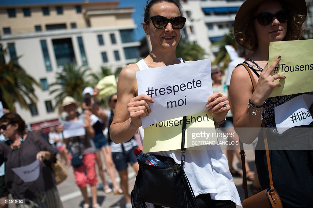 A woman holds signs reading 'All in shorts' and 'Freedom' during the 'Marche des Shorts' (The March of the Shorts) to show support to a young woman who was attacked in a bus because she wearing shorts, in Toulon, southeastern France, on June 25, 2016. / AFP / BERTRAND