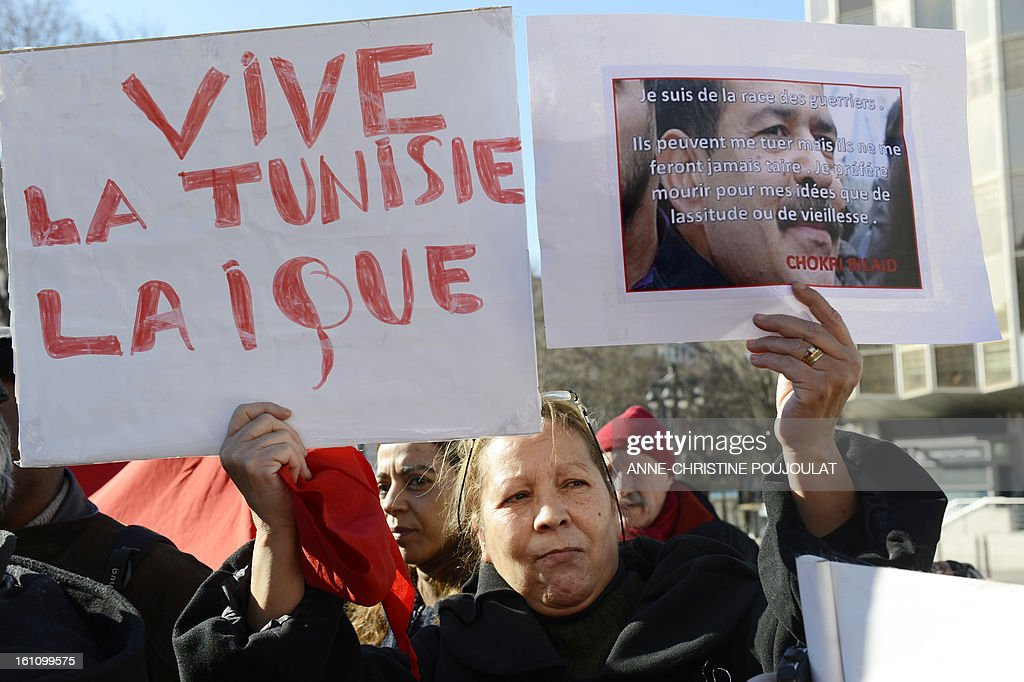 A woman holds signs reading at left 'long live secular Tunisia' and a portrait of murdered opposition figure Chokri Belaid reading ''I am a warrior. They can kill me but they will never shut me down. I prefer to die for my ideas rather than tiredness and old age' during a protest to pay tribute to Belaid on February 9, 2013, in Marseille, southern France. The shooting of Belaid, a leftist leader and outspoken government critic by a lone, hooded gunman on February 6, 2013 plunged Tunisia into new post-revolt turmoil as tension and division within the Ennahda party itself intensified.