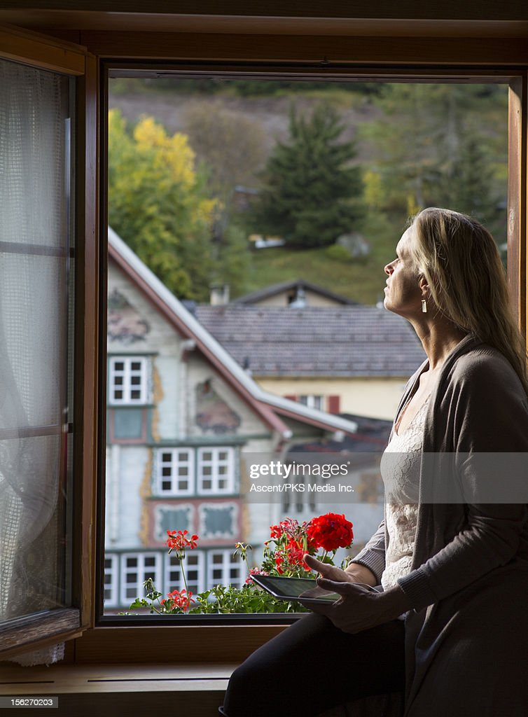 Woman holds tablet, looks out from hotel window : Stock Photo