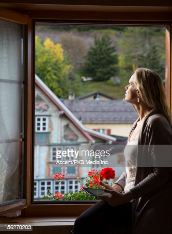 Woman holds tablet, looks out from hotel window : Stock-Foto