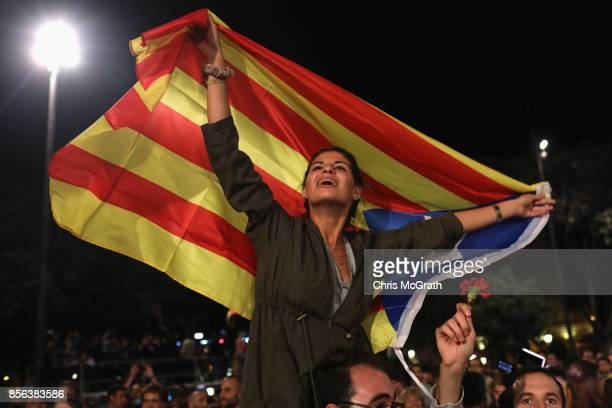 A woman holds the Catalan flag as crowds gather to await the result of the Indepenence Referendum at the Placa de Catalunya on October 1 2017 in...