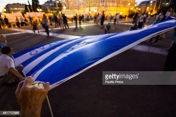A woman holds the edge of a giant Greek flag in front of the Parliament Unions gather outside the Parliament to protest against the ongoing voting of...