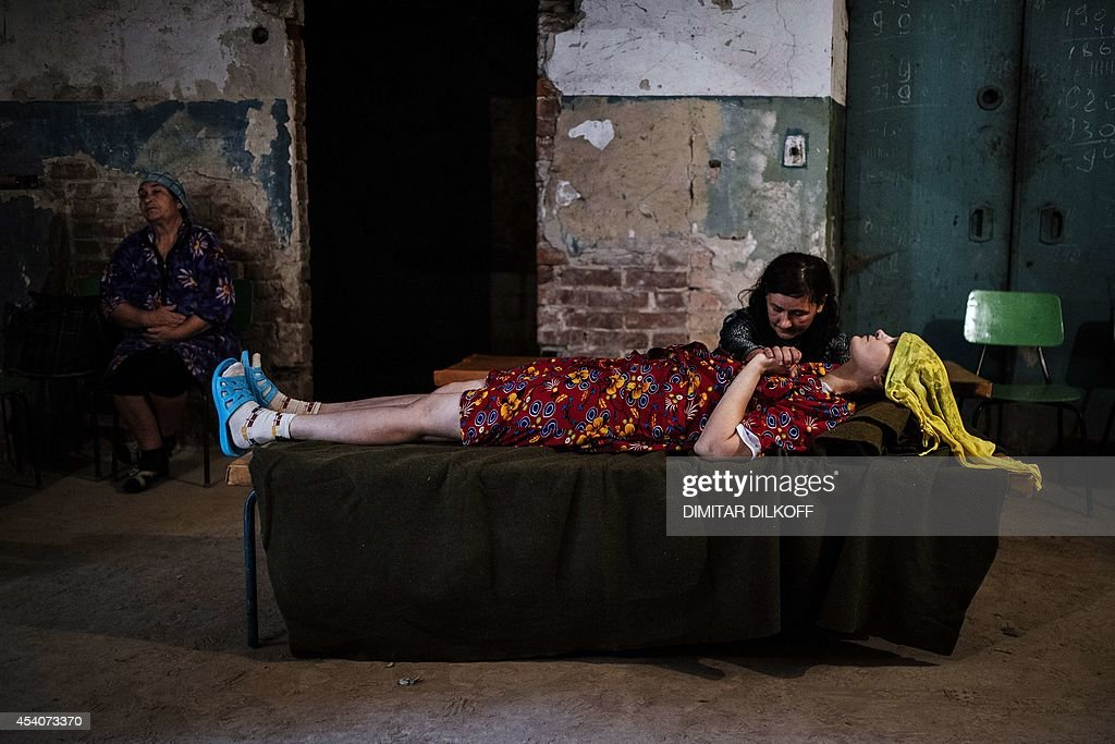 ? woman holds the hand of her sick friend in the basement of Kalinina hospital after shelling on August 24, 2014 in Donetsk, eastern Ukraine. Pro-Russian rebels in eastern Ukraine paraded dozens of captured soldiers before a jeering crowd on August 24 in a bid to mock Kiev's Independence Day celebrations. In the capital, the Ukrainian government had sought to boost morale and send a defiant message to the rebels with an upbeat military parade to mark the country's independence from the Soviet Union in 1991.