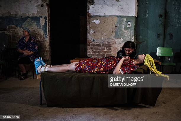 woman holds the hand of her sick friend in the basement of Kalinina hospital after shelling on August 24 2014 in Donetsk eastern Ukraine ProRussian...