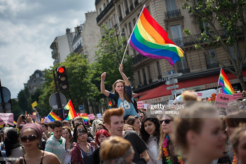 A woman holds the rainbow flag, colors of pride for the gay community during the homosexual, lesbian, bisexual and transgender (HLBT) visibility march, the Gay Pride, on June 29, 2013 in Paris, exactly one month to the day since France celebrated its first gay marriage. AFP PHOTO / MARTIN BUREAU