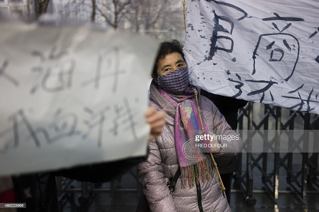 A woman holds up a banner as a group protests about alleged local government wrongdoing and unpaid wages outside the Langfang Court where the verdict...
