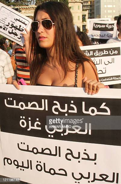 A woman holds up a banner written in Arabic that reads 'The way Arab silence slaughtered Gaza the Arab silence is slaughtering Hama today' during a...