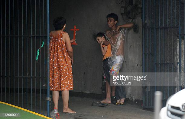 A woman holds up a cross towards hostage taker Remer Parparan as he points an icepick at 10 years old Jason Pineda during a hostage taking incident...