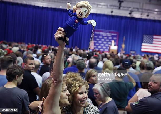 A woman holds up a doll in the likeness of Democratic presidential nominee Hillary Clinton while Republican presidential candidate Donald Trump...