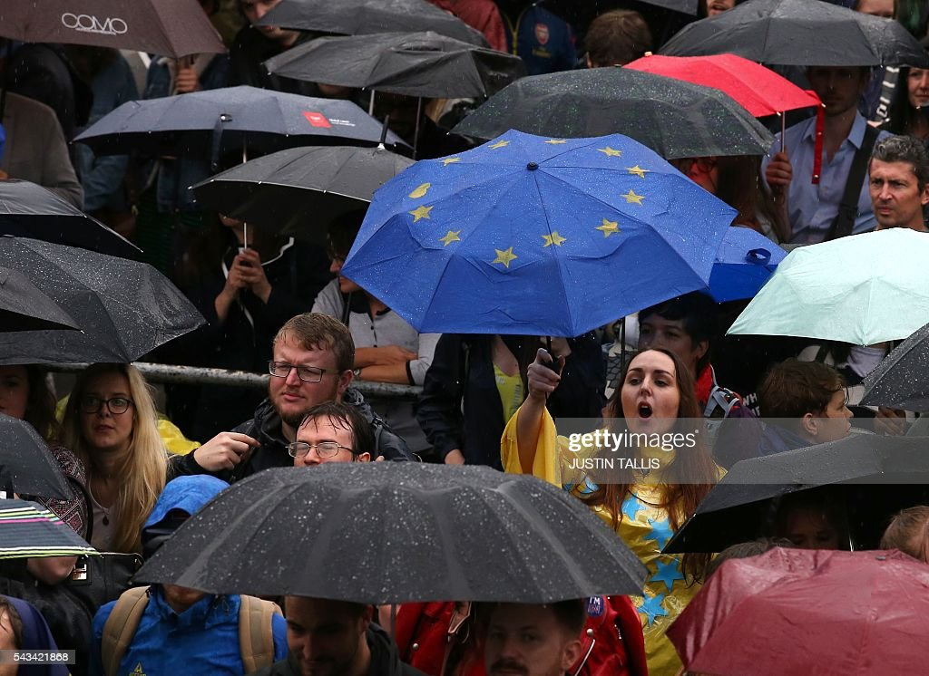 A woman holds up a European flag umbrella as demonstrators shelter from the rain at an anti-Brexit protest in Trafalgar Square in central London on June 28, 2016. EU leaders attempted to rescue the European project and Prime Minister David Cameron sought to calm fears over Britain's vote to leave the bloc as ratings agencies downgraded the country. Britain has been pitched into uncertainty by the June 23 referendum result, with Cameron announcing his resignation, the economy facing a string of shocks and Scotland making a fresh threat to break away. / AFP / JUSTIN