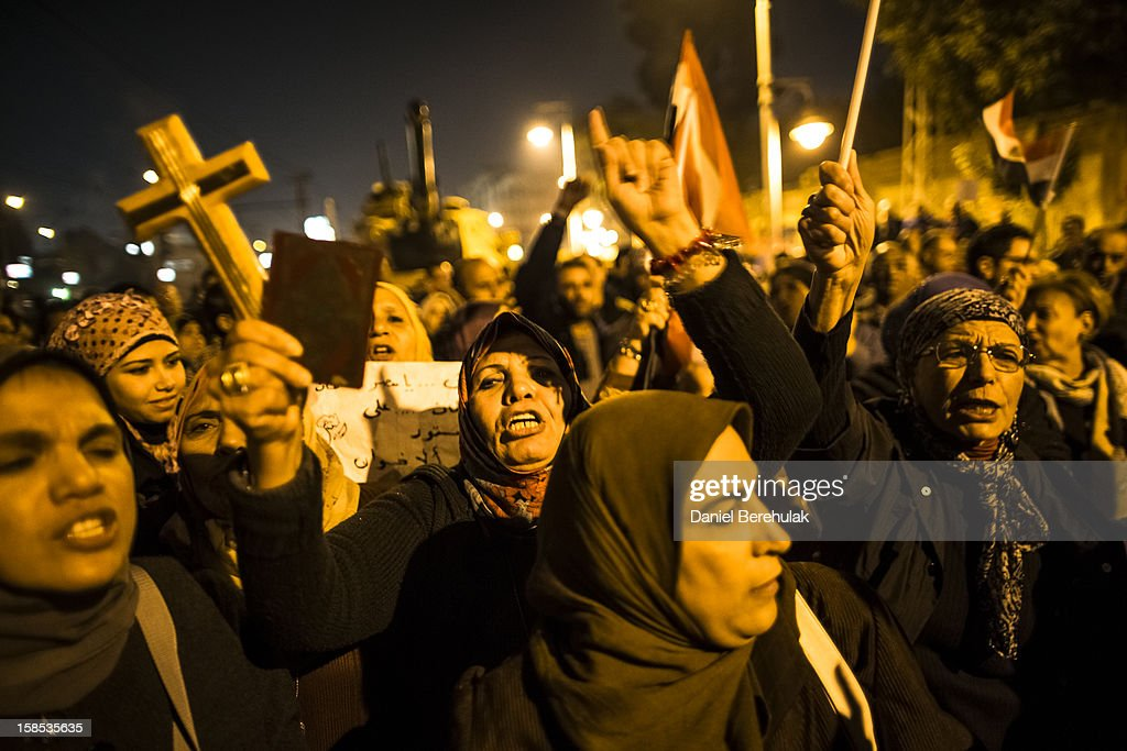 A woman holds up a Koran and a cross in her hand as Egyptian protestors opposing President Mohammed Morsi chant slogans during a demonstration at the Presidential Palace on December 18, 2012 in Cairo, Egypt. Hundreds of people gathered in front of the Presidential Palace and in Tahrir Square to protest against President Mohammed Morsi and the alleged rigging of the first round of voting in the constitutional referendum.