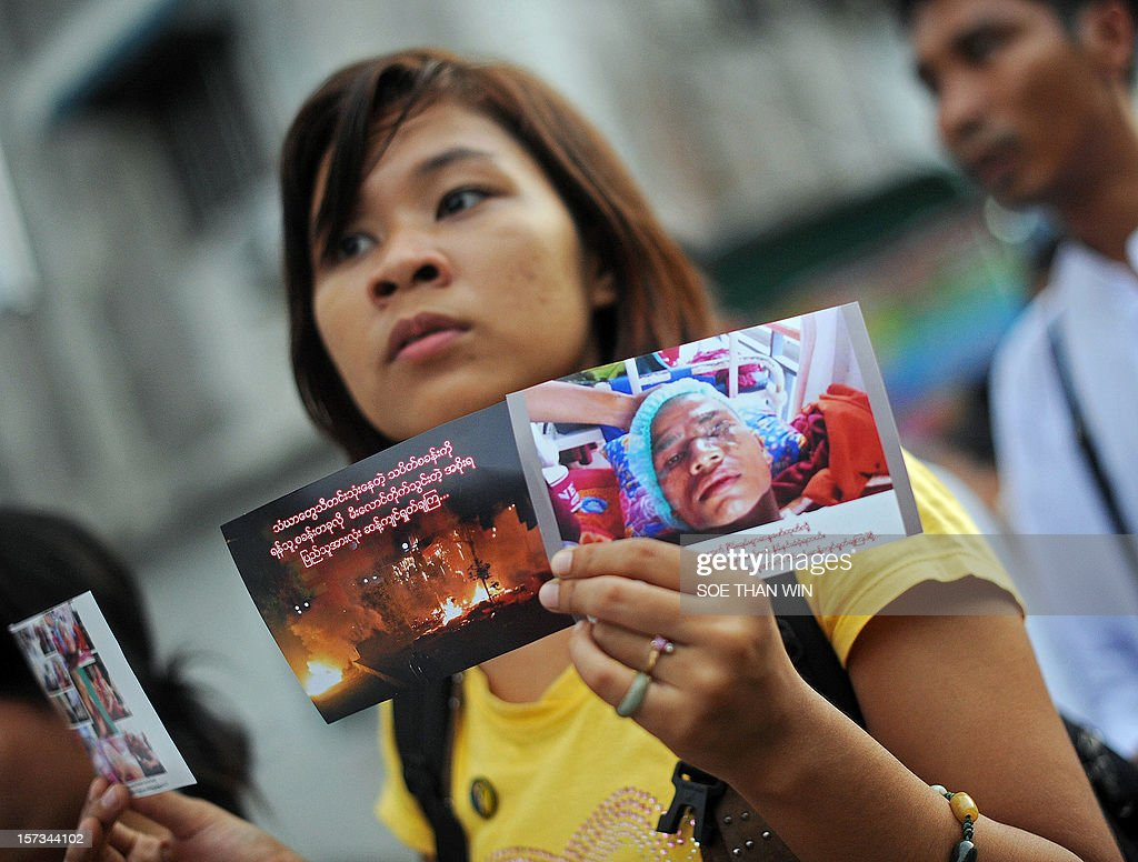 A woman holds up a photo of an injured Buddhist monk during a protest in Yangon on December 2, 2012 against a Chinese-backed copper mine in Monywa in northern Myanmar. At least two people have been arrested at a rally in Yangon held to condemn a violent police crackdown on protesters at a Chinese-backed copper mine, an activist and an AFP reporter said. AFP PHOTO / Soe Than WIN