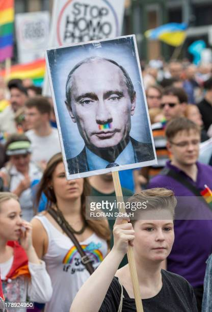 A woman holds up a picture showing Russian President Vladimir Putin with a rainbow colored mustache in Berlin on August 31 2013 during a...