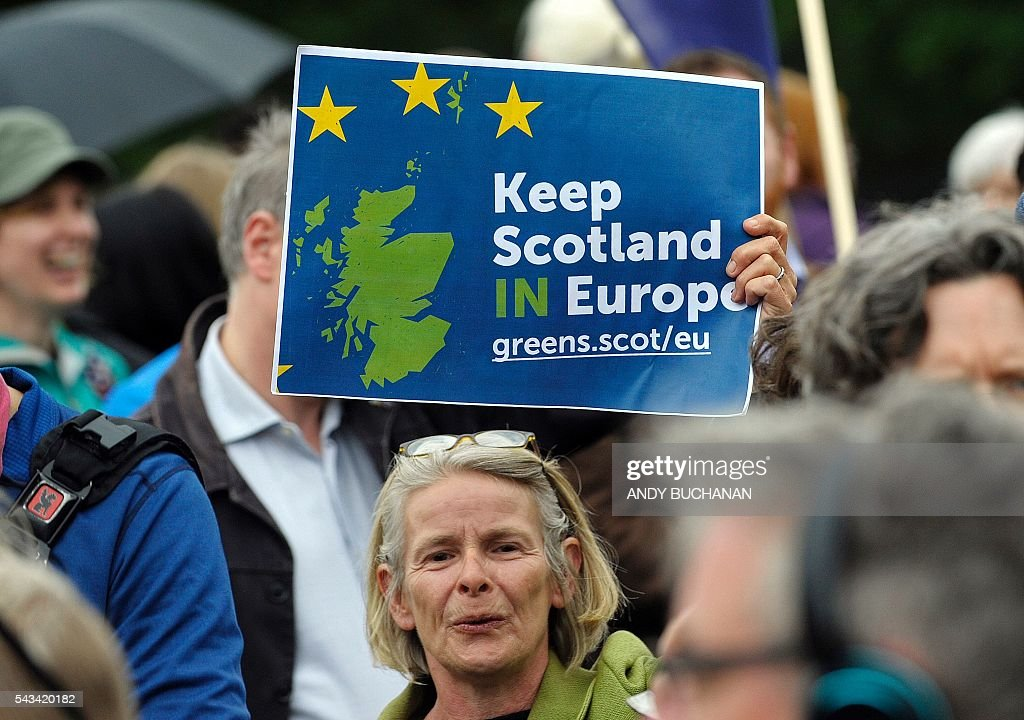 A woman holds up a placard at a demonstration by Pro EU campaigners outside the Scottish Parliament ahead of a debate on the EU Referendum result and the implications for Scotland, in Edinburgh, Scotland on June 28, 2016. Scottish First Minister Nicola Sturgeon said she would travel to Brussels on Wednesday for talks to defend Scotland's place in the European Union after a vote by Britain as a whole to leave the bloc. Sturgeon said she was 'utterly determined' to protect Scotland as she asked an emergency session of the Scottish parliament on Tuesday for a formal mandate for direct talks with the European Union institutions. / AFP / Andy Buchanan