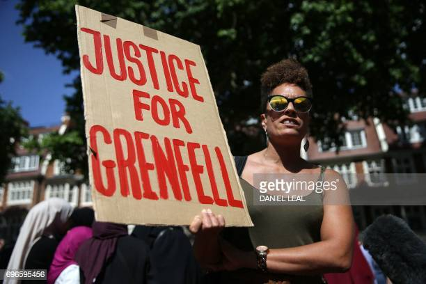 A woman holds up a placard calling for 'Justice for Grenfell' during a protest outside Kensington Town Hall on June 16 justice for those affected by...