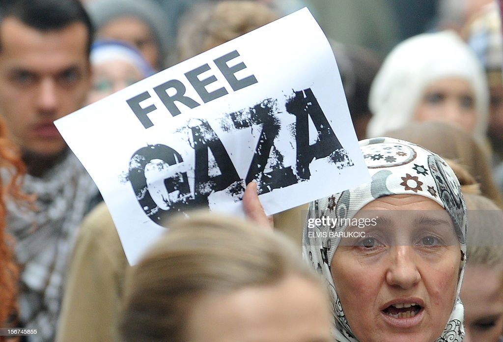 A woman holds up a poster during a march on November 20, 2012, through the center of Sarajevo in support of Palestinian people following the latest Israeli attacks in Gaza. Israel's air force dropped leaflets across Gaza City on Tuesday urging people to evacuate their homes 'immediately' amid fears the military was poised to launch a ground operation. The violence comes as Israel heads towards a general election in January, raising the spectre of a broader Israeli military campaign along the lines of its devastating 22-day Operation Cast Lead launched at the end of December 2008.