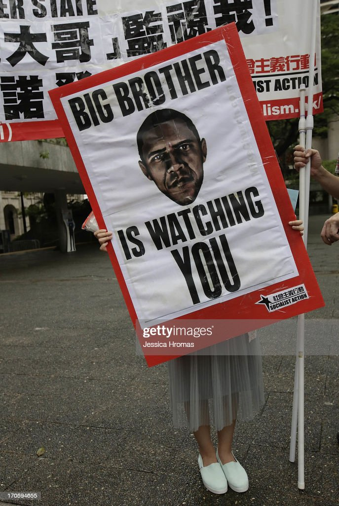 A woman holds up a protest sign in Charter Garden, Central, Hong Kong at the start of the protest rally in support of Edward Snowden, on June 15, 2013 in Hong Kong, Hong Kong. Former CIA employee Edward Snowden is accused of leaking details of top-secret US surveillance of phones and internet.