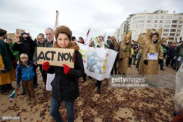 A woman holds up a sign as demonstrators gather for the 'Climate March' protest on December 6 2015 in Oostende during the COP21 United Nations...