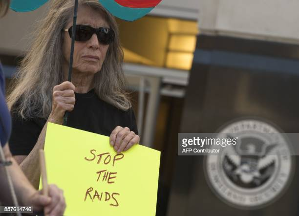 A woman holds up a sign during a protest against US Immigration and Customs Enforcement raids outside the ICE office part of the Department of...