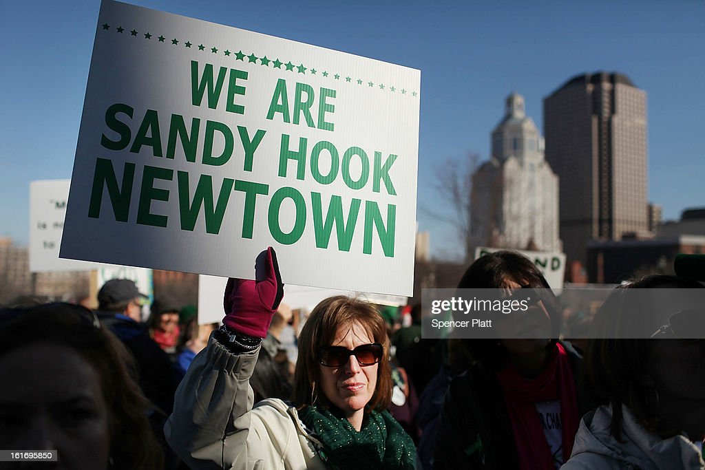 A woman holds up a sign during a rally at the Connecticut State Capital to promote gun control legislation in the wake of the December 14, 2012, school shooting in Newtown on February 14, 2013 in Hartford, Connecticut. Referred to as the 'March for Change' and held on the two-month anniversary of the massacre in Newtown, Connecticut, participants called for improved gun safety laws. Among the safety measures being demanded are for universal background checks, more work within the mental health community and restricting high-capacity magazines.