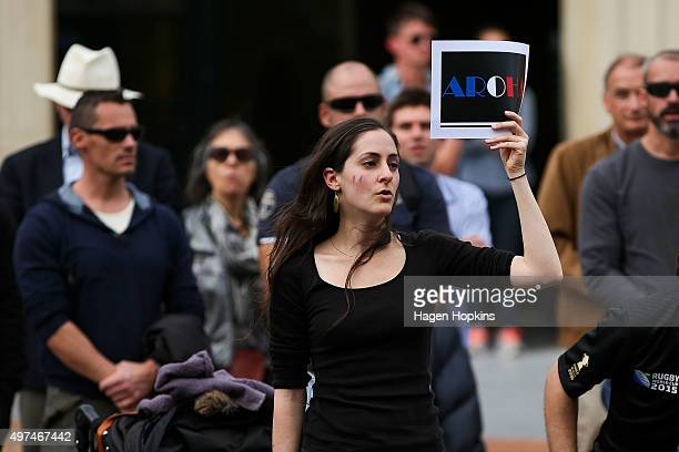 A woman holds up an 'Aroha' sign meaning love in Maori while starting to sing the French national anthem during a memorial for victims of the Paris...