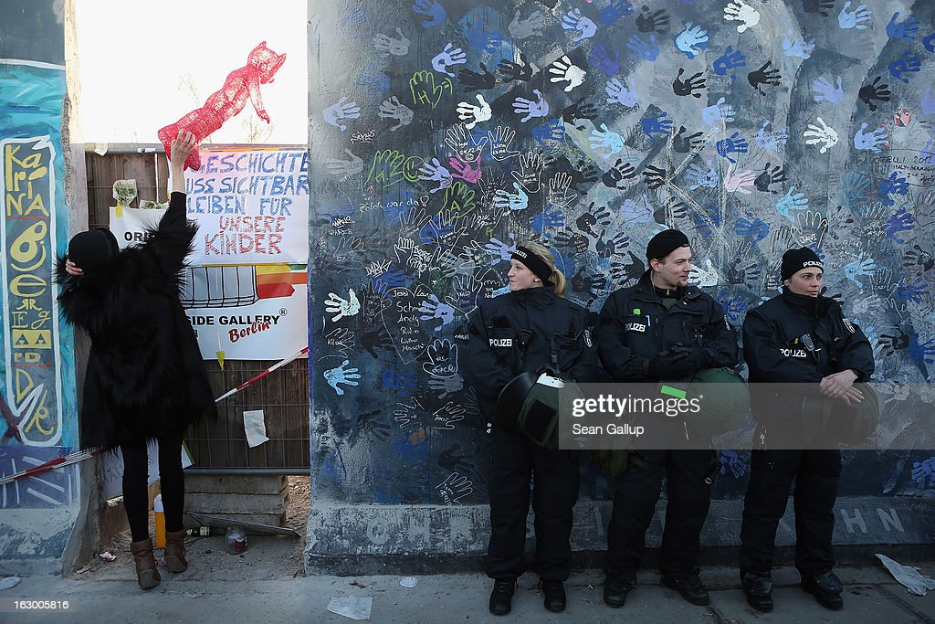 A woman holds up an effigy of a red fox as police in riot gear stand guard at a section of the East Side Gallery, which is the longest still-standing portion of the former Berlin Wall, that is to be removed tomorrow by a construction company building a high-rise luxury apartment block on March 3, 2013 in Berlin, Germany. A real estate developer is planning to build a 14-storey apartment building between the East Side Gallery and the Spree River and needs to remove the Wall section in order to allow access to the construction site. Protesters managed to temporarily halt the dismantling of the section on March 1. Critics, including East Side Gallery mural artists and Spree River embankment development opponents, decry the move, citing the importance of the East Side Gallery's status as a protected landmark and a major tourist attraction. The East Side Gallery is approximately 1.3 kilometers long.