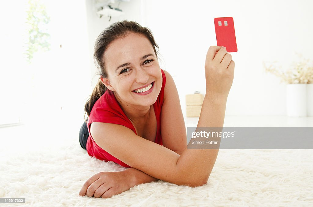 Woman holds up credit card : Stock Photo