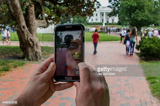 A woman holds up her cell phone as she plays the Pokemon Go game in Lafayette Park in front of the White House in Washington DC July 12 2016 Pokémon...