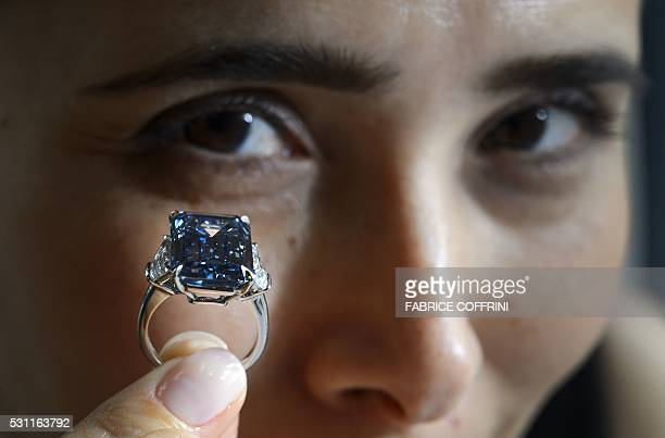 A woman holds up the 'Oppenheimer Blue' a rare fancy vivid blue diamond weighing 1462 carat during a press preview by Christies's auction house on...