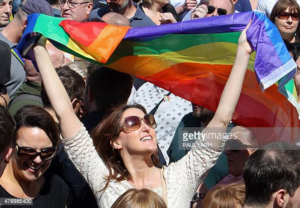 A woman holds up the rainbow flag a gay pride flag as thousands of people gather at Belfast city hall at a rally for gay marriage rights on June 13...