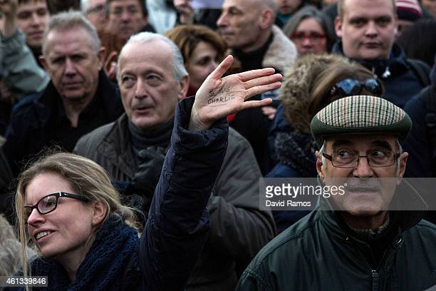 A woman holds up the words 'Je Suis Charlie' on her hand as demonstrators make their way along Place de la Republique during a mass unity rally...