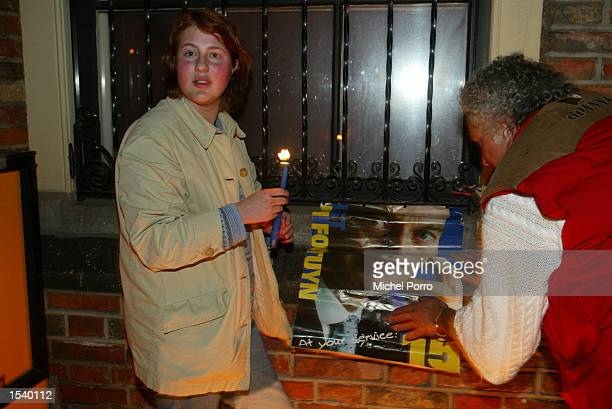 A woman holds vigil as a man attaches a poster on the wall of the parliament building for slain controversial Dutch rightwing politician Pim Fortuyn...
