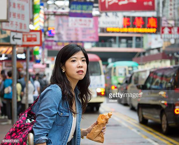 Woman Hong Kong, eating traditional fast food, getting taxi