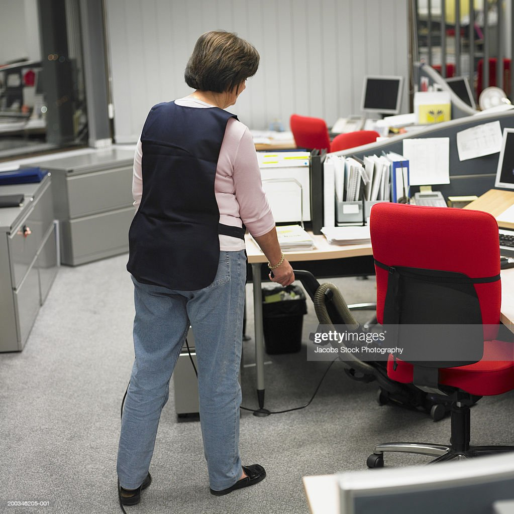 Woman hoovering under desk in office, rear view : Stock Photo