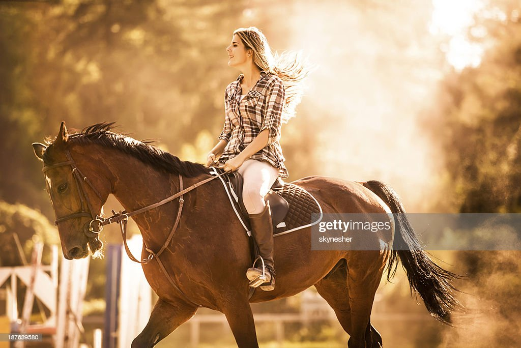 Woman horseback riding at sunset.