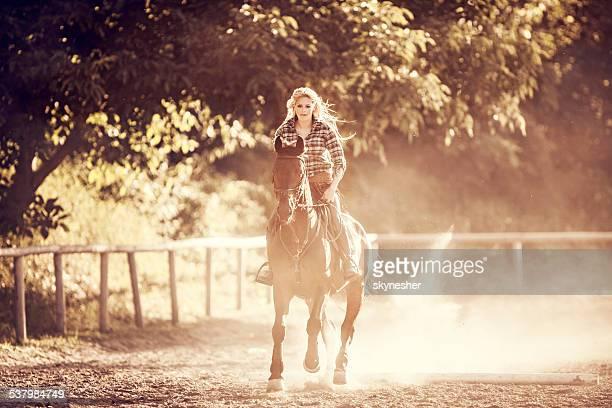 Woman horseback riding at sunset.